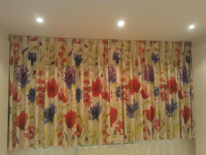 Top fixed rail with cord, blackout lined, pinch pleats in a bedroom